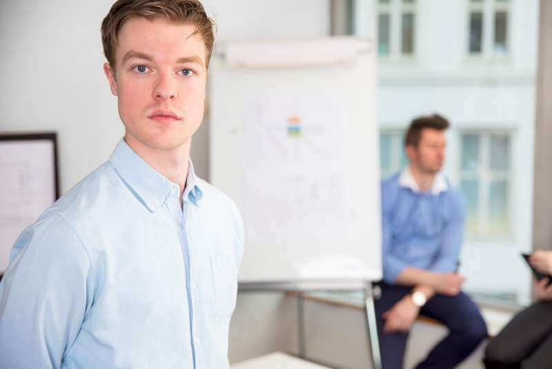 confident-young-businessman-standing-in-office