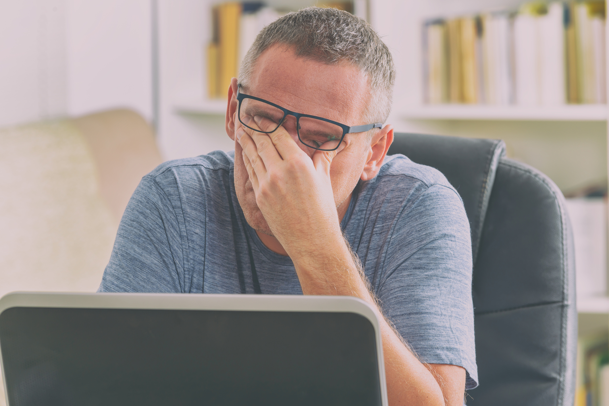 Tired man rubbing his eyes while working with laptop