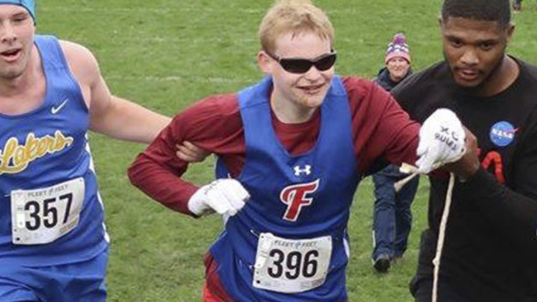 Cazenovia High School sophomore Jake Tobin, left, helps Fairport High School senior Luke Fortner, center, during a cross country race in Auburn, N.Y. Fortner, who is legally blind, fell towards the end of the race but was assisted by Tobin, and Jerry Thompson, right, his running aide.