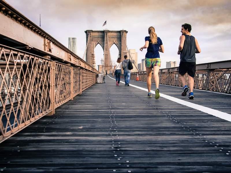 young couples running bridge