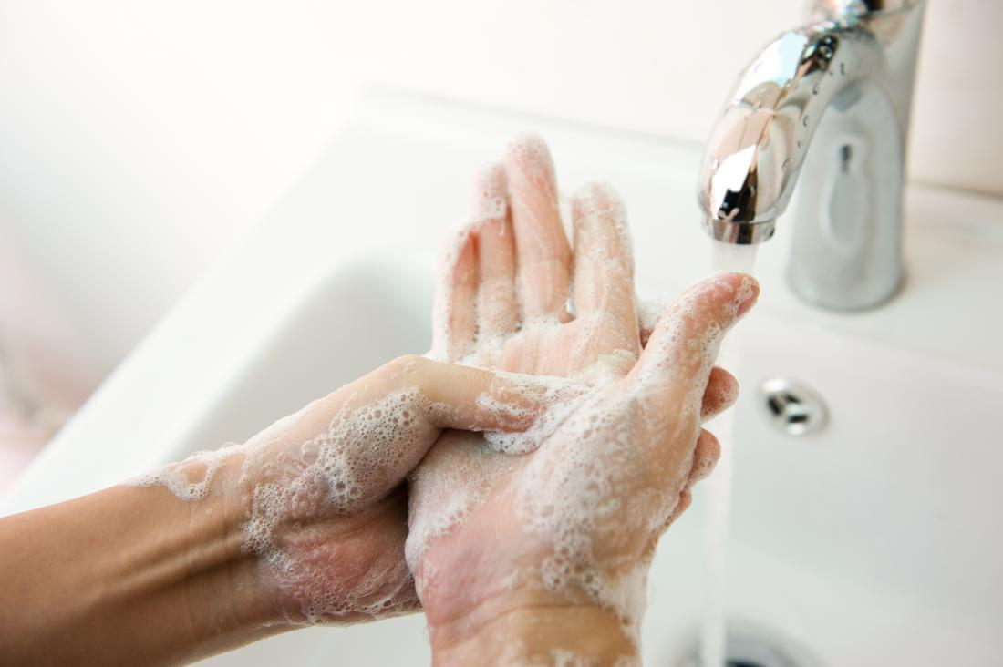 Person washing hands with soapy running water