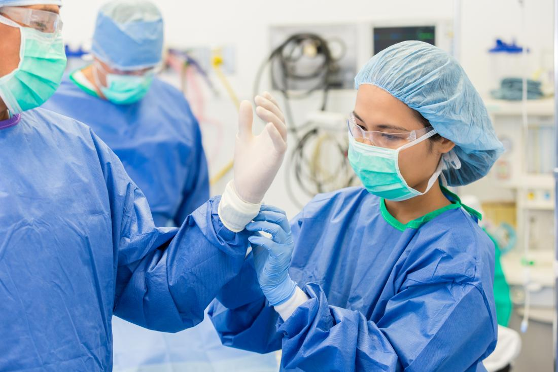 Surgeon wearing mask, protective eyewear, hair net, gown, and helping other surgeon with sterile gloves before operation.