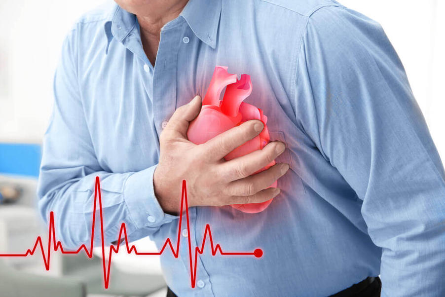 man clutches chest having a heart attack