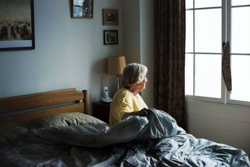 senior-woman-sitting-in-a-bedroomjpg