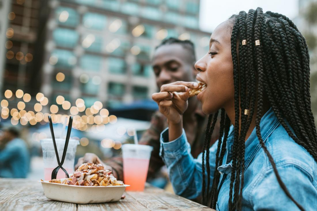close up of woman eating junk food