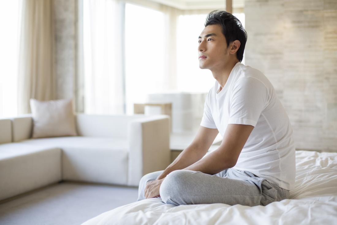 Man with dry skin on penis sitting on bed