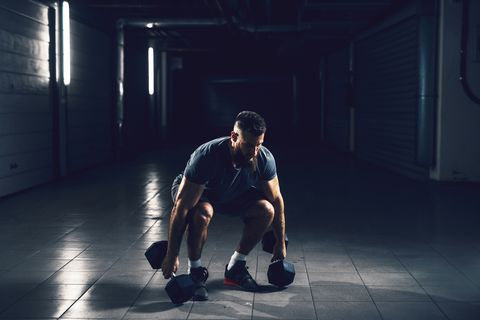 Close up view of focussed hardworking active fitness strong muscular bearded bodybuilder man crouching before raising heavyweight dumbbell in the underground garage or urban gym while looking far away.